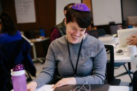 Rabbi Lauren Tuchman sits at a table and studies from a Braille Talmud